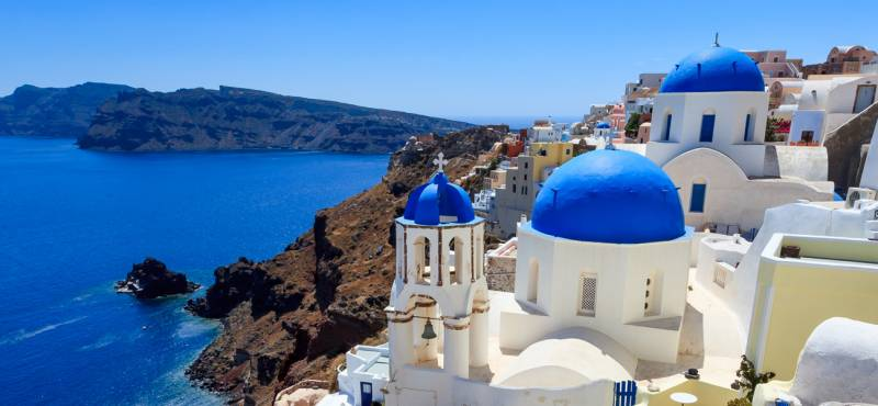 The blue-domed and white washed houses of Santorini island in Greece