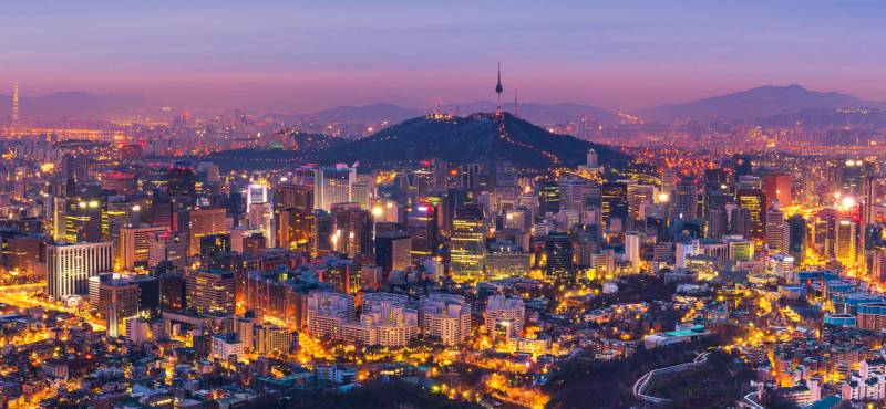 The skyline of Seoul in South Korea at dusk with the city lights gleaming