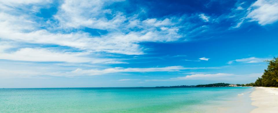 Clouds swirling in the blue sky over the white powder sand and turquoise sea in Sihanoukville
