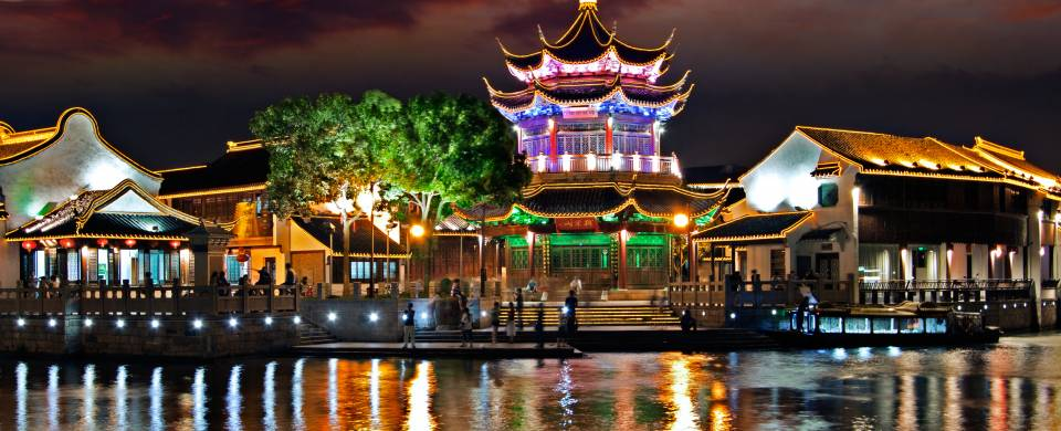 View of Suzhou lit up at night from across the water