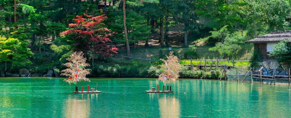 Beautiful, turquoise water surrounded by lush forest in Takayama