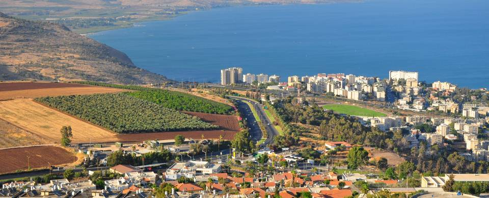 Dazzling blue water of Sea of Galilee running along the edgy of the Jewish Holy City of Tiberias