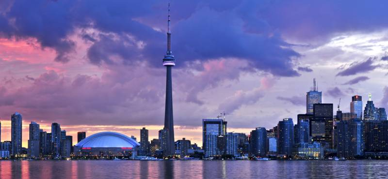 The skyline of Toronto with a colourful sunset and the CN Tower standing tall