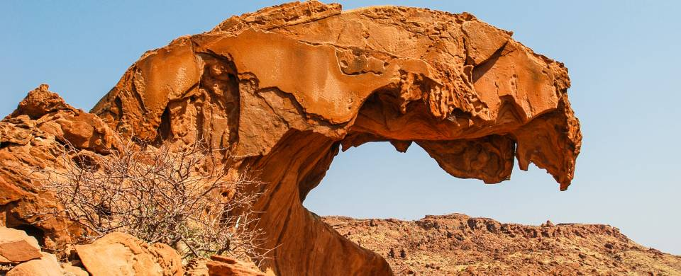 Curved rock against a bright blue sky at Twyfelfontein