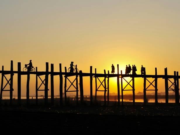 Sunset staining the sky orange as people walk along the U Bein Bridge in Mandalay
