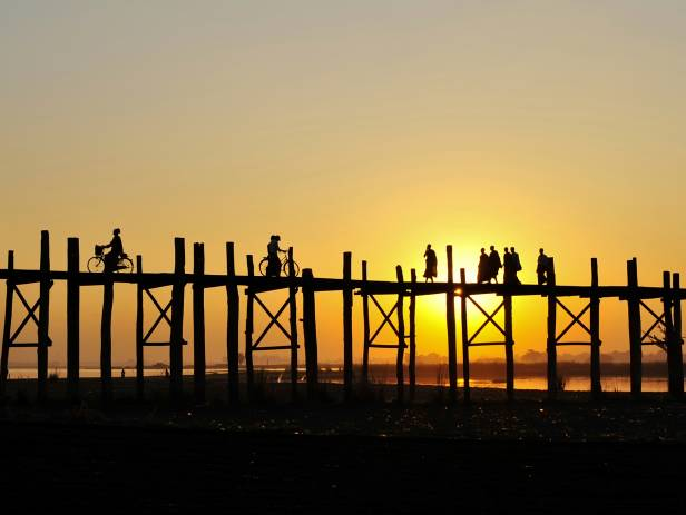 Sunset staining the sky orange as people walk along the U Bein Bridge in Mandalay