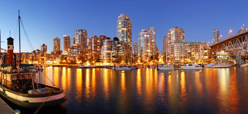 The attractive skyline of Vancouver at dusk with the city lights reflecting in the water
