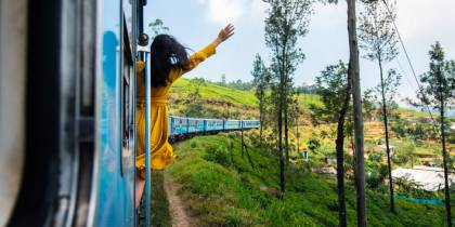 Woman enjoying train ride through Sri Lanka tea plantations